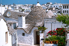 """Unique White Buildings With Conical Roof Called """"Trulli"""" In Alberobello Small Town And Comune Of The Metropolitan City Of Bari, Puglia, Southern Italy."""