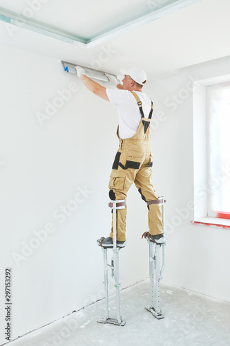 Painter in stilts with putty knife Canvas Print