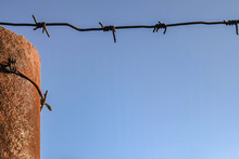 Rusty Metal Pole Wrapped In Barbed Wire Against Blue Sky. Close-up. Copy Space.