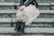 Woman in pink lace skirt with white flowers bouquet in her hands is sitting on stairs.
