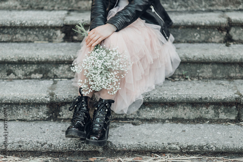 Woman in pink lace skirt with white flowers bouquet in her hands is sitting on stairs Tablou Canvas