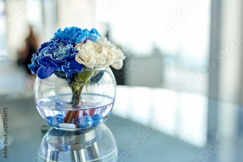 Spoed Fotobehang Orchidee Blue and white orchids in a vase on the table, a beautiful arrangement of flowers in the office.