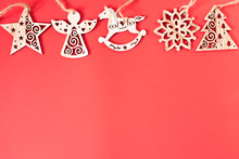 Festive Little Wooden Christmas Toys Over The Red Background With Copy Space For Text And Xmas Decoration. Top View, Copy Space, Mockup