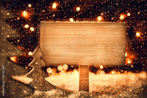 Christmas Tree On Snow And Fairy Lights In Background. Retro Wooden Sign With Copy Space For Advertisement.