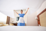 Pretty young chamber maid in uniform stretching white clean linen over bed