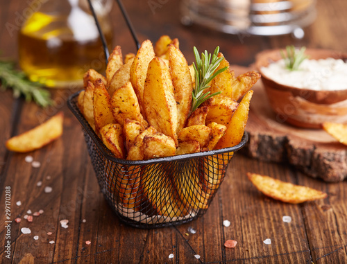 Fototapeta Potato wedges baked with rosemary. Delicious snack served with sauce. Fast food. obraz