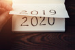 canvas print picture - New Year 2020 coming concept. Male fingers flips notepad or calendar sheet. 2019 is turning, 2020 is opening, top view