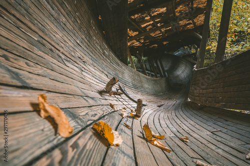 Photo sur Toile Route dans la forêt Abandoned luge track in pine woods. Wooden bobsleigh track curves along the trees with vintage luge sled on the track covered in leaves. Outdated sport complex in Murjani, Latvia.
