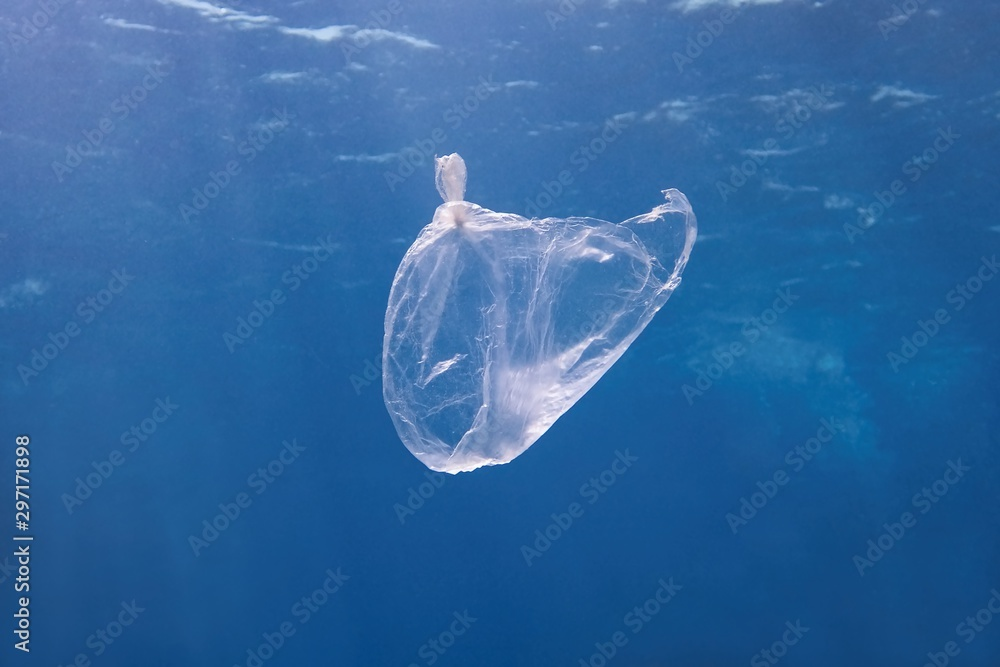 Fototapety, obrazy: Plastic bag floating in the blue sea water. World ocean contaminated by  plastic. Environment pollution concept.