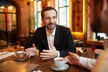 Portrait Of Successful Mature Businessman Pitching Idea To Partner And Smiling During Meeting In Luxurious Cafe