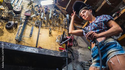 Fotografía  Welder girl. A girl with a welding machine welds metal.