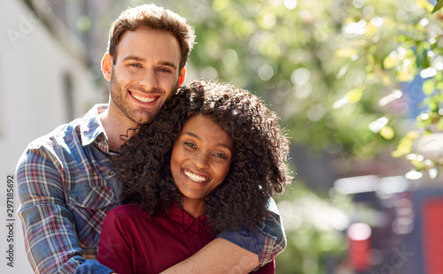 Diverse couple affectionately standing together ouside on a sunny day Wallpaper Mural
