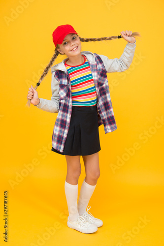 Getting your hairstyle to last all day. Happy child with braided hairstyle yellow background. Small cute girl smile with long hairstyle. Fashion look of pigtailed hairstyle