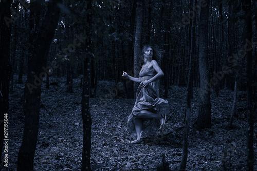 Fotografía Scared girl running through forest