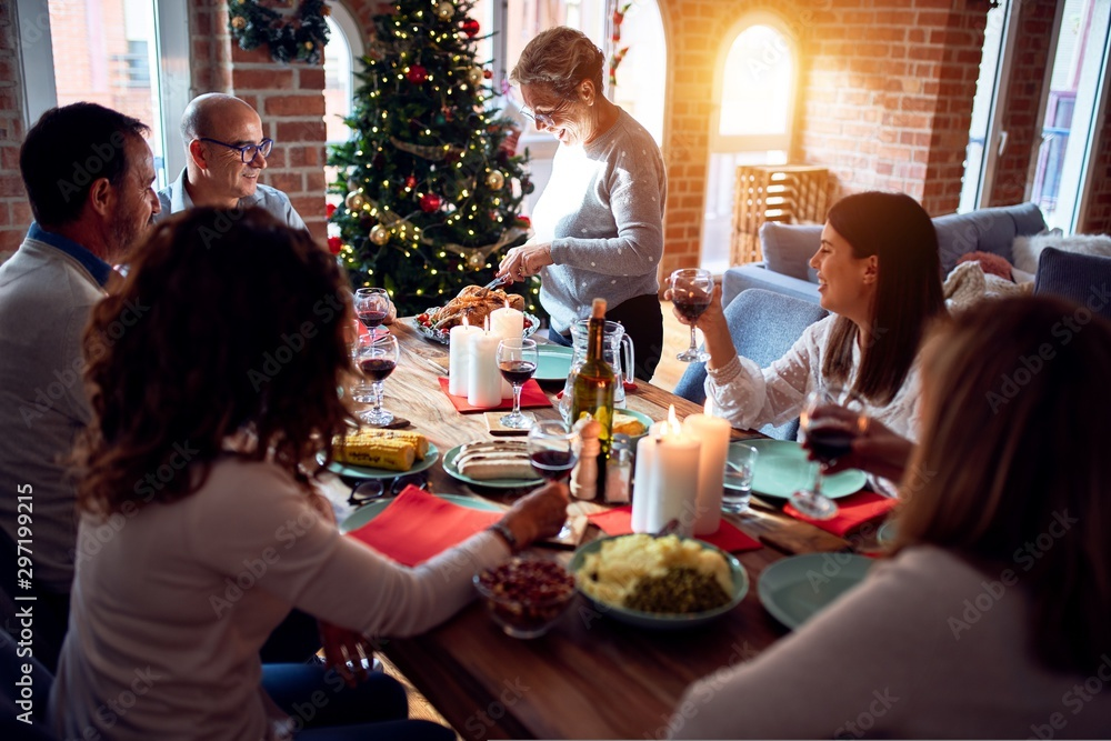 Fotografie, Obraz Family and friends dining at home celebrating christmas eve with traditional foo