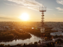 Communication Tower On City And Sunset Background.
