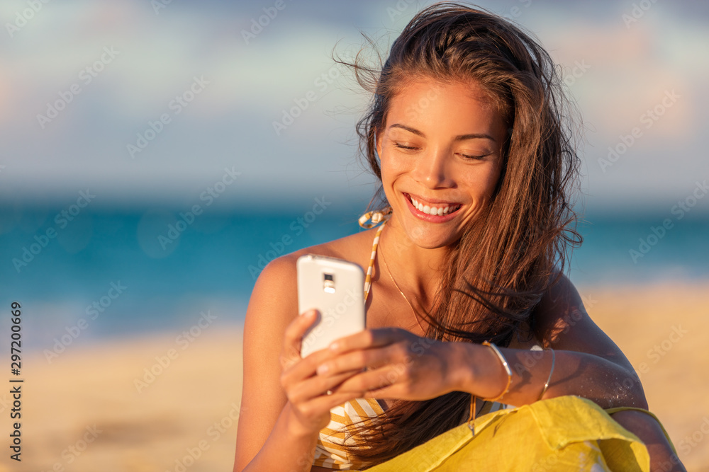 Fototapety, obrazy: Happy young Asian woman using mobile phone texting online on beach vacation holiday travel summer lifestyle, Smiling multiracial chinese girl tourist relaxing on holidays.