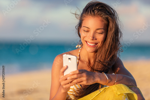 Cadres-photo bureau Akt Happy young Asian woman using mobile phone texting online on beach vacation holiday travel summer lifestyle, Smiling multiracial chinese girl tourist relaxing on holidays.
