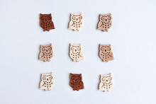 Flat Lay Pattern Of Nein Cute Wooden Owls Set With Tree Diferents Colors Of Wood Light To Dark On White Background. Wood Carving Concept.