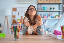 Young Beautiful Teacher Woman Wearing Sweater And Glasses Sitting On Desk At Kindergarten Hugging Oneself Happy And Positive, Smiling Confident. Self Love And Self Care