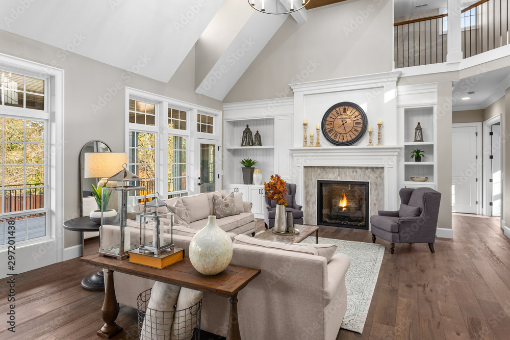 Fototapety, obrazy: Beautiful living room in new traditional style luxury home. Features vaulted ceilings, fireplace with roaring fire, and elegant furnishings.