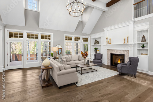 Beautiful living room in new traditional style luxury home. Features vaulted ceilings, fireplace with roaring fire, and elegant furnishings.