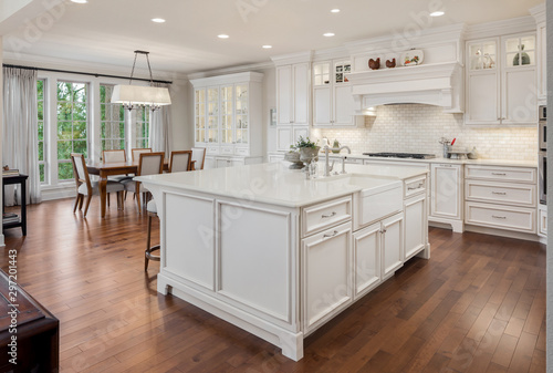 Fototapeta Beautiful kitchen in new traditional style luxury home, with large island, double ovens, cook top, and open concept floor plan. Shows dining area with dining table obraz