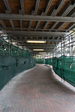 Pedestrian Path Through A Construction Site With Green Fabric Sides, Metal Scaffolding, Brick Paving, And Fluorescent Lighting
