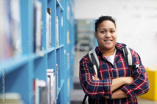 Leinwand Poster  Waist up portrait of mixed-race college student wearing backpack and smiling at