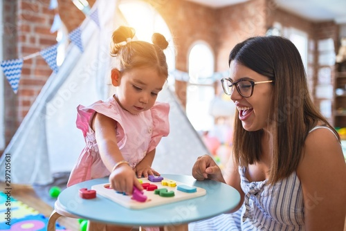 Obraz Young beautiful teacher and toddler learning maths playing with numbers puzzle at kindergarten - fototapety do salonu