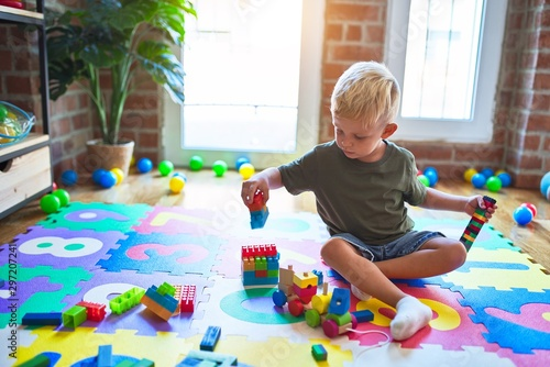 Canvastavla  Young caucasian kid playing at kindergarten with toys