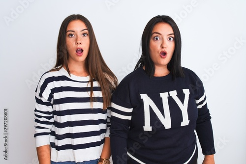 Fototapeta  Young beautiful women wearing casual clothes standing over isolated white background afraid and shocked with surprise expression, fear and excited face
