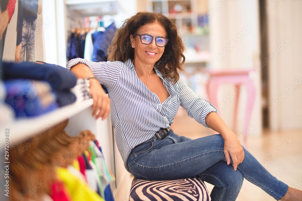 Fototapety, obrazy: Middle age beautiful businesswoman wearing striped shirt and glasses smiling happy and confident sitting on bench at clothes shop