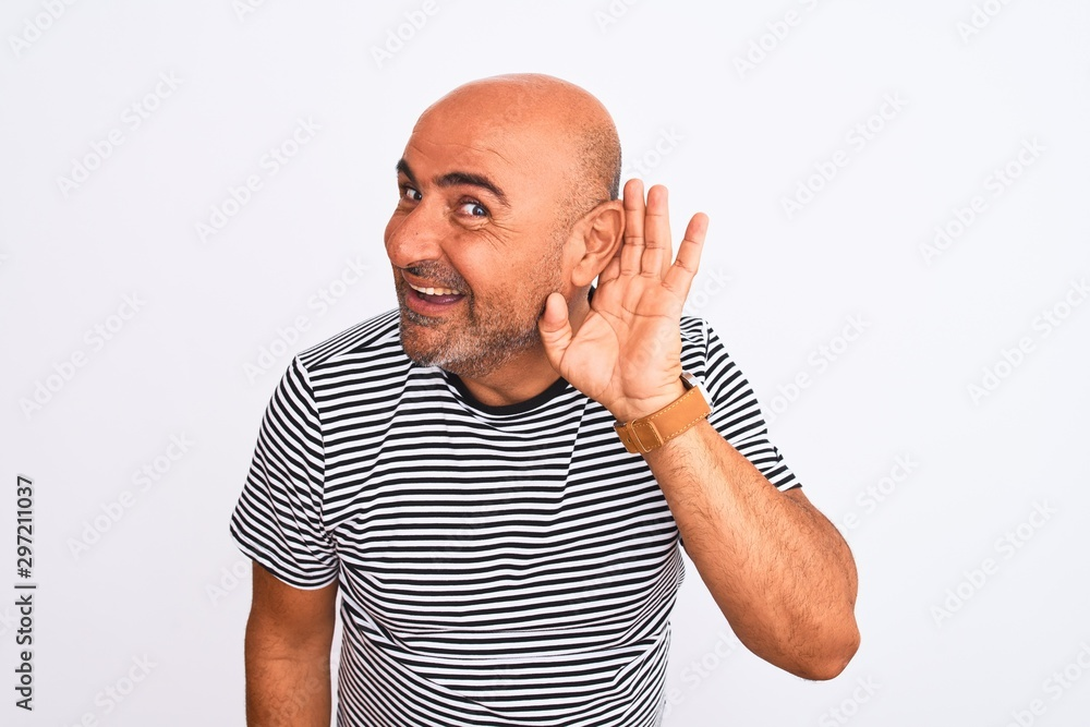 Fototapety, obrazy: Middle age handsome man wearing striped navy t-shirt over isolated white background smiling with hand over ear listening an hearing to rumor or gossip. Deafness concept.