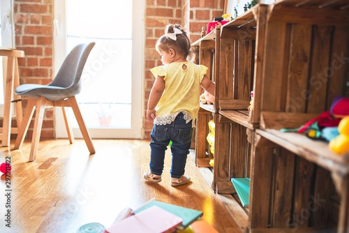 Fototapety, obrazy: Beautiful toddler standing around lots of toys at kindergarten