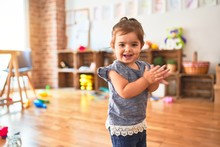 Beautiful Toddler Standing On The Floor Applauding And Smiling At Kindergarten