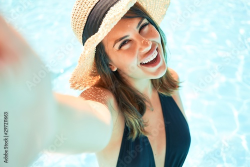 Fotomural  Young beautiful and sexy woman at the hotel pool taking a selfie smiling using s