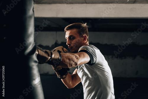 Fit professional boxing man kicking at punching bag Fototapete