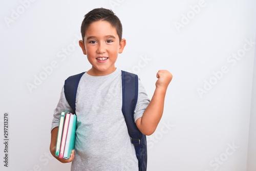 Beautiful student kid boy wearing backpack holding books over isolated white bac Fototapet
