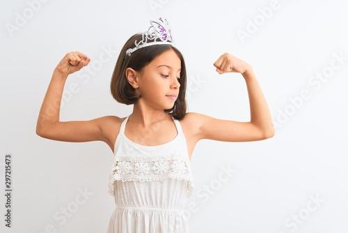 Piękna dziecko dziewczyna jest ubranym princess koronę stoi nad odosobnionym białym tłem pokazuje ręka mięśni ono uśmiecha się dumny. Koncepcja fitness.