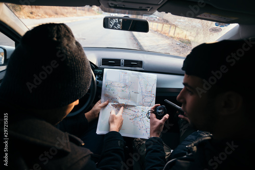 Fotomural  Bank robbers,planning their next hit while holding a gun and counting on a stop watch the time they need to get from one point on the map to another one