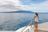 Cruise ship tourist on luxury yacht looking at sea nature landscape in Galapagos Islands while sailing on boat enjoying luxury travel lifestyle.