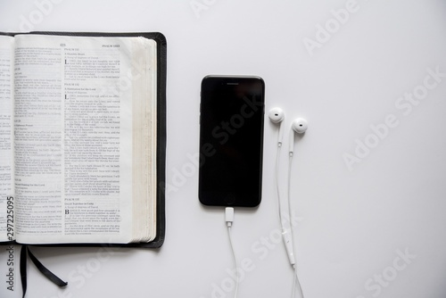 Photo Overhead shot of a smartphone with headphones near an open bible on a white surf