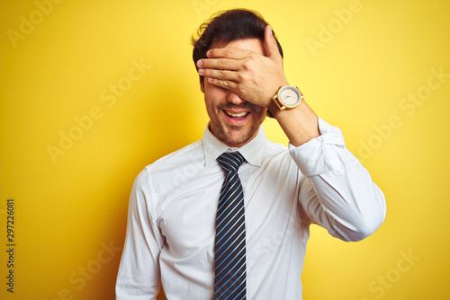 Stampa su Tela  Young handsome businessman wearing elegant shirt and tie over isolated yellow background smiling and laughing with hand on face covering eyes for surprise