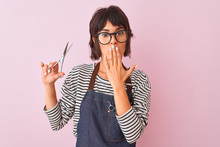 Hairdresser Woman Wearing Apron And Glasses Holding Scissors Over Isolated Pink Background Cover Mouth With Hand Shocked With Shame For Mistake, Expression Of Fear, Scared In Silence, Secret Concept