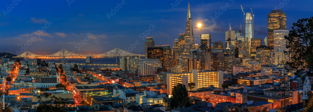 Fototapeta San Francisco skyline panorama at dusk with Bay Bridge and downtown skyline under a full moon