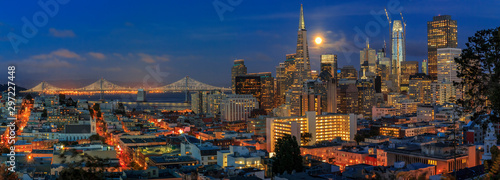 San Francisco skyline panorama at dusk with Bay Bridge and downtown skyline under a full moon