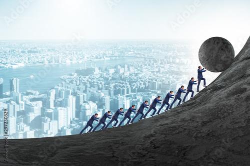 Obraz na plátně Team of people pushing stone uphill