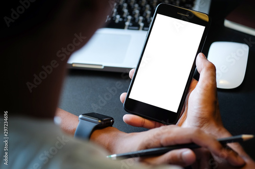 Obraz Cropped shot view of man hands holding smart phone with blank copy space screen for your text message or information content, female reading text message on cell telephone during in urban setting.  - fototapety do salonu