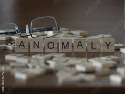 Fototapeta  The concept of Anomaly represented by wooden letter tiles